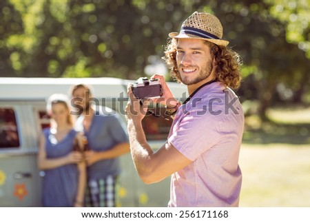 Hipster taking a photo of his friends on a summers day - stock photo