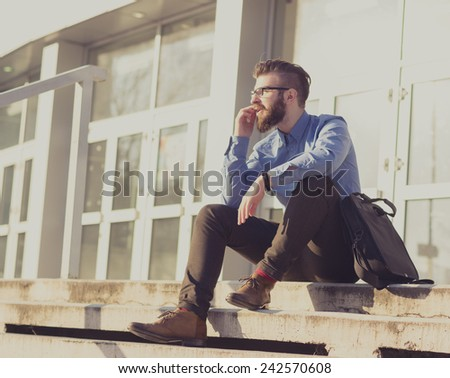 Hipster talking on the phone and sitting on stairs - stock photo