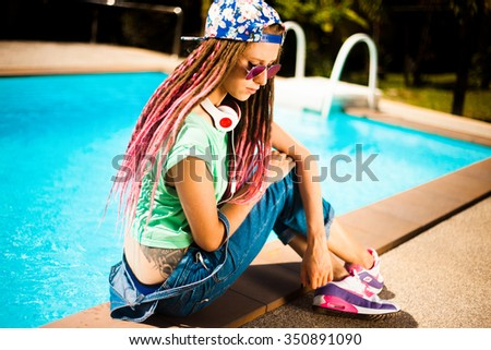 Hipster teen girl,wear swag cap,enjoy music on her big headphones,earphones,mirrored sunglasses,colorful sneakers and outfit,denim jeans, swagger cloth,fashionable teen style,new fashion hairstyle - stock photo