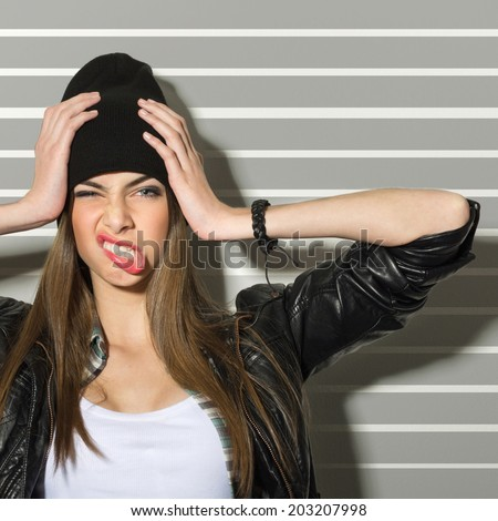 Hipster teenage girl making faces and holding her head wearing black beanie hat, leather jacket and bracelet against gray stripes background. - stock photo