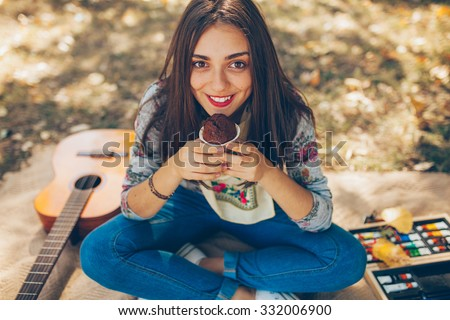 Hipster teenager girl smiling and sitting outdoors with guitar and color palet. Creative artistic young woman wearing casual clothes having a picnic on autumn day. - stock photo