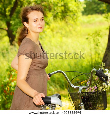 Hipster teenager with a bicycle and with wild flowers in a basket