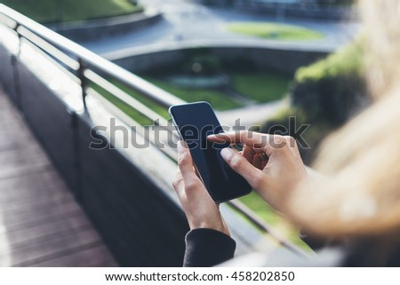 Hipster texting message on smartphone or technology, mock up of screen. Tourist girl using cellphone on bridge background. Female hands holding gadget on blurred backdrop. Mockup copy space for text - stock photo