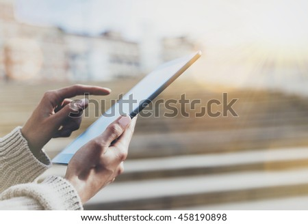 Hipster tourist texting message on tablet or technology mock up. Person using computer on building background close. Female hands holding gadget, blur flare mockup. Copy space for text message design - stock photo