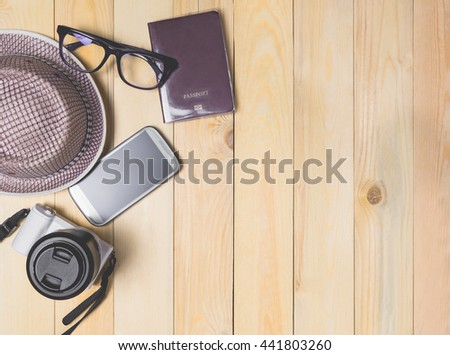 Hipster Traveler equipment items on wooden background.