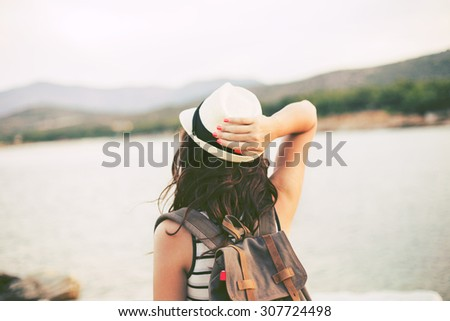 Hipster Traveler with backpack and outspread hands near sea at sunrise. Enjoying sun, deep breathing  - stock photo