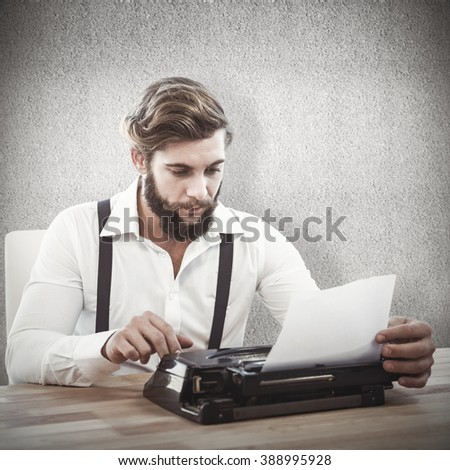 Hipster using typewriter at desk in office against grey wall