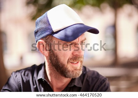Hipster with beard and baseball cap sitting in a street cafe looking seriously
