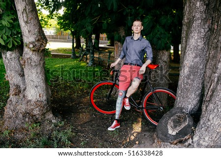 Hipster with red bycicle and tattoo on leg