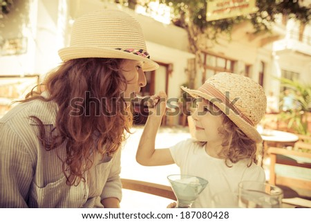 Hipster woman and girl in summer cafe - stock photo