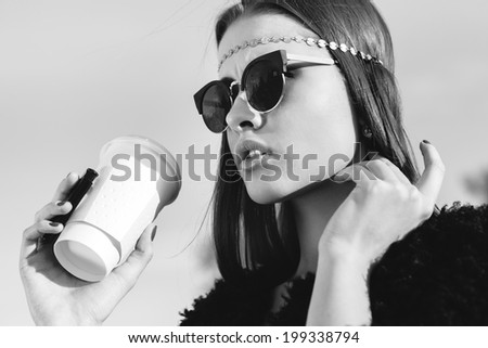Hipster woman in sunglasses with cup of coffee. Close-up black and white lifestyle outdoor portrait - stock photo