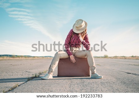 Hipster woman in the hat sits on suitcase on road