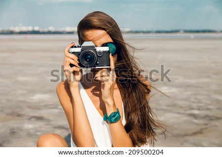 Hipster woman taking photos with retro film camera on the field. - stock photo