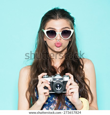 Hipster woman taking photos with retro film camera on the field and make funny face. - stock photo