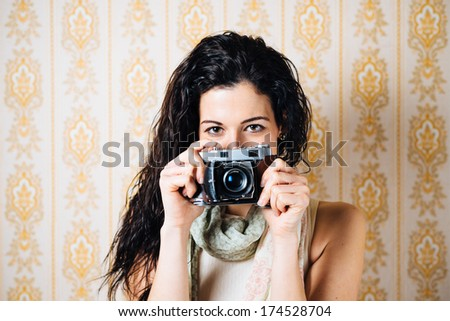Hipster woman taking photos with retro film camera on vintage ornamental wallpaper. - stock photo