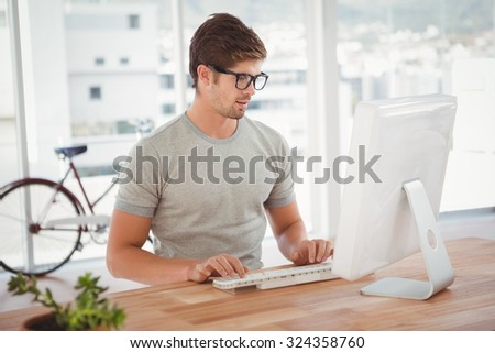 Hipster working on computer at desk in office - stock photo