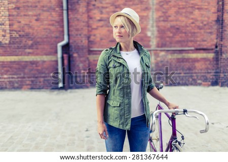 Hipster young beautiful girl with vintage road bike in city, urban scene. Stylish beauty woman cycling on fixed gear bike in town, retro city street industrial background. - stock photo
