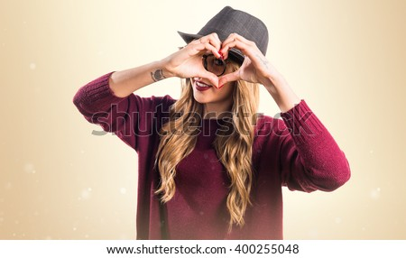 Hipster young girl making a heart with her hands - stock photo