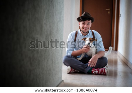 hipster young man posing with jack russell dog in a hallway - stock photo