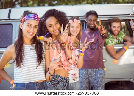 Hipsters hanging out by camper van at a music festival - stock photo