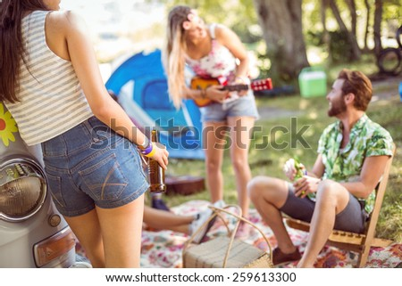 Hipsters having fun in their campsite at a music festival - stock photo