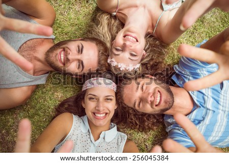 Hipsters lying on grass smiling on a summers day