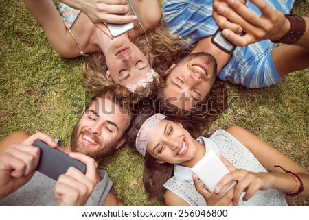 Hipsters lying on grass using smartphones on a summers day