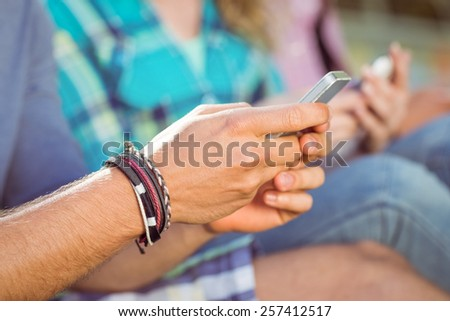 Hipsters sitting on the grass texting on a summers day