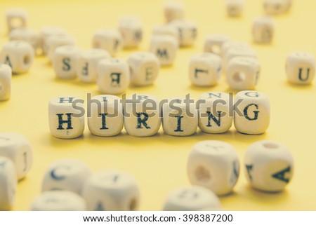 HIRING word written on wood block. Wooden Abc - stock photo