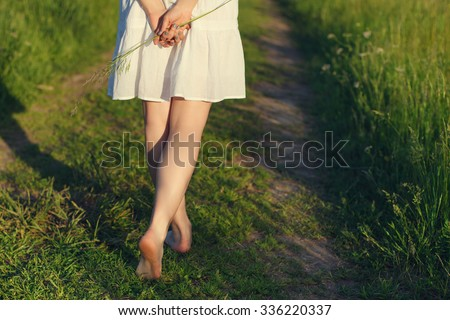 His bare feet beautiful woman close up are on a rural road.