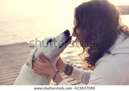 His owner dog licks gently, loving gesture - stock photo