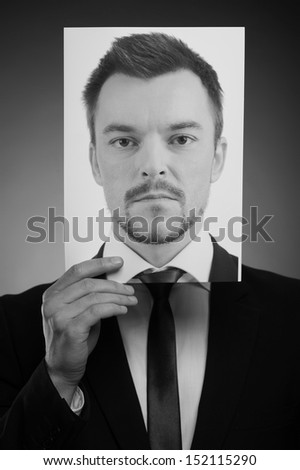 His today mask. Black and white image of man in formalwear holding a photograph of serious man in front of his face - stock photo