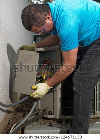 Hispanic aircon maintenance man - stock photo