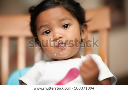 Hispanic baby girl learning to eat by herself with milk spilled on her mouth - stock photo