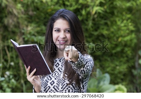 Hispanic brunette in park environment wearing formal clothing holding book open while pointing into camera and smiling.