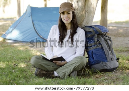 Hispanic brunette writing on a journal about her hiking trip
