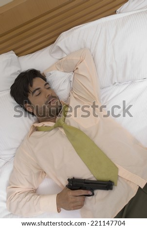 Hispanic businessman holding gun in bed - stock photo