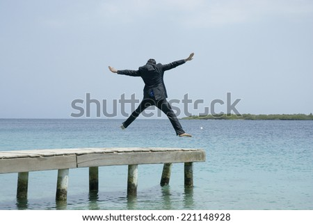 Hispanic businessman jumping on dock - stock photo