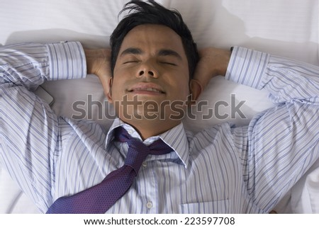 Hispanic businessman laying on bed - stock photo