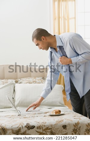 Hispanic businessman looking at laptop