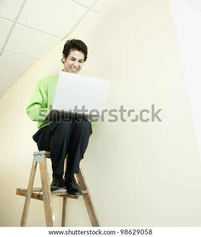 Hispanic businessman on ladder looking at laptop
