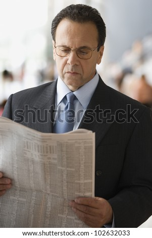Hispanic businessman reading newspaper