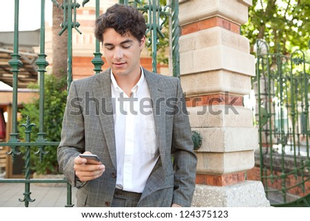Hispanic businessman using a smart phone while standing in the corner of a classic city street.