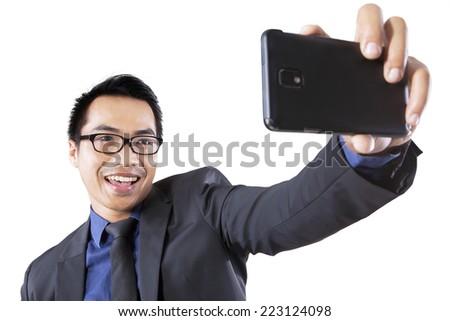 Hispanic businessman using smartphone to take picture of himself - stock photo