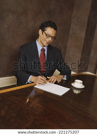 Hispanic businessman writing
