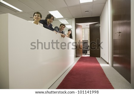 Hispanic businesspeople looking over cubicle wall - stock photo