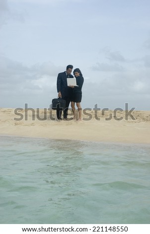 Hispanic businesspeople with laptop at beach - stock photo