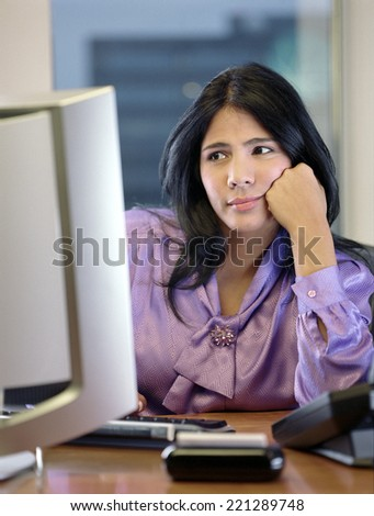 Hispanic businesswoman looking at computer - stock photo