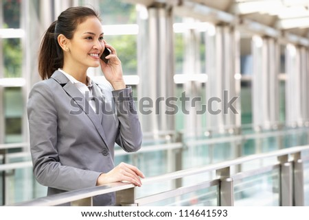 Hispanic Businesswoman Outside Office On Mobile Phone