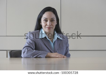 Hispanic businesswoman sitting at table
